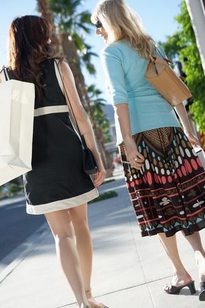 shopping trip: Women walking outside carrying shopping bag on Shopping Trip back view