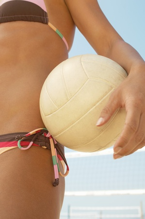 unknown age: Beach volleyball player in bikini holding volleyball outdoors mid section