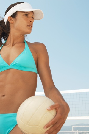 Beach volleyball player in bikini holding volleyball outdoors Stock Photo - 8837057
