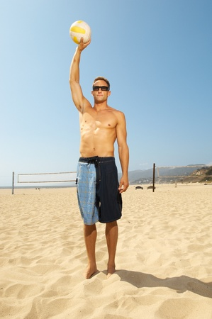 unknown men: Young man in shorts standing on beach holding volleyball above head
