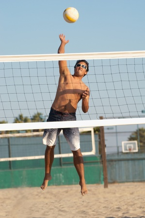 Young man jumping hitting volleyball over net on beach Stock Photo - 8837060