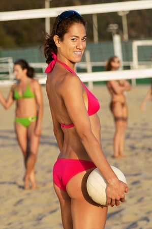 unknown age: Beach volleyball player in bikini holding volleyball outdoors