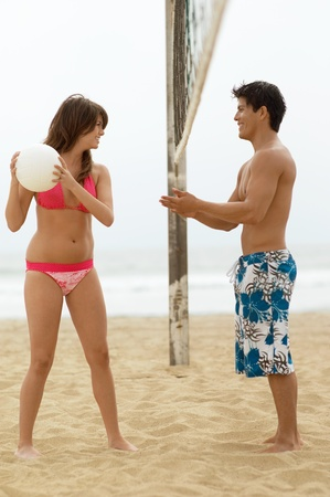 Young Woman Teasing Boyfriend with ball on Beach volleyball net between them Stock Photo - 8837070