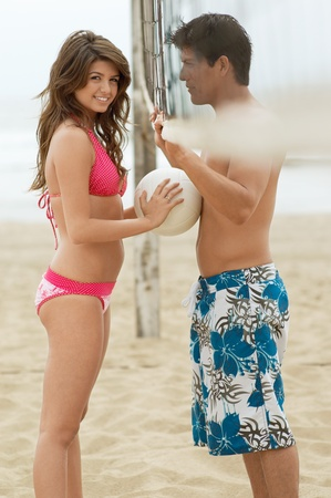 swimming shorts: Couple Flirting on Beach with volleyball net between them woman holding ball against her boyfriend