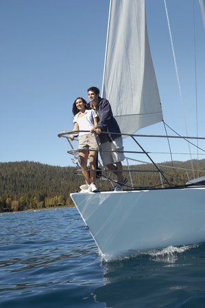 long lake: Young couple standing on bow of sailboat