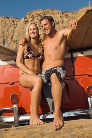 leaning on the truck: Young couple in swimwear leaning on back of truck with surfboards