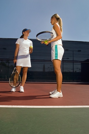 doubles: Tennis Doubles Partners Discussing Strategy on tennis court LANG_EVOIMAGES