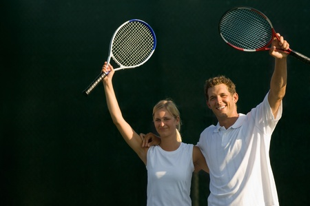 Tennis Partners standing side by side arms around Raising Rackets in Victory Stock Photo - 8837181