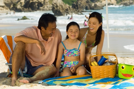 Parents with daughter (7-9) having picnic on beach Stock Photo - 8837205