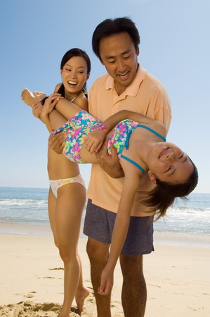 Parents carrying daughter (7-9) on beach Stock Photo - 8837208