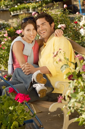 Couple embracing at plant nursery (portrait) Stock Photo - 8837254