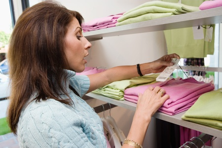 Woman looking at price tag on clothing side view Stock Photo - 8837270
