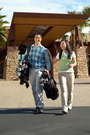 Man Carrying Girlfriend's Golf Clubs outside of golf clubhouse Stock Photo - 8837278