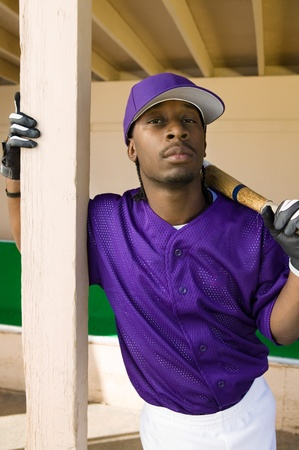 baseball dugout: Baseball player holding bat in dugout (portrait)