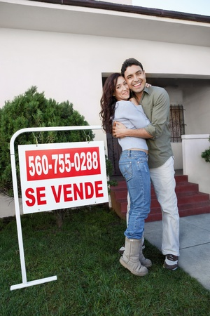 spanish houses: Couple standing in front of house with For Sale sign portrait