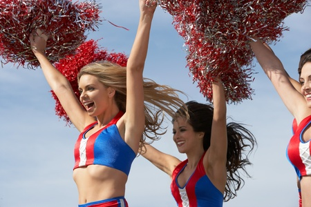Cheerleaders running holding pom poms in air Stock Photo - 8837345