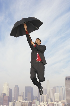 at ease: Business man floating away on umbrella above city