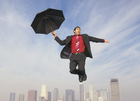 Business man floating away on umbrella above city Stock Photo - 8837378