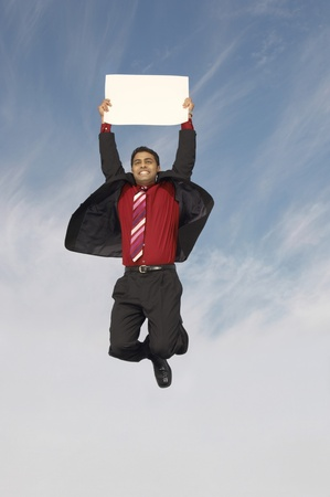 Business man jumping with blank sign outdoors Stock Photo - 8837379