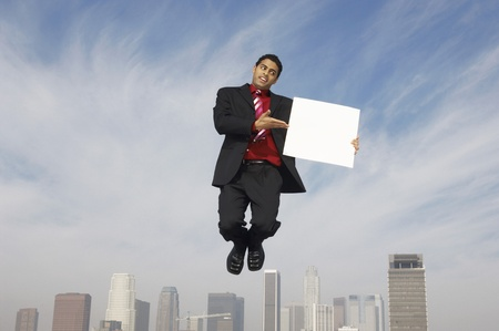 Business man jumping with blank sign above city Stock Photo - 8837380