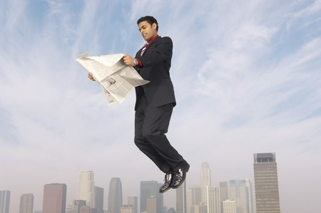 midair: Business man reading newspaper mid-air above city