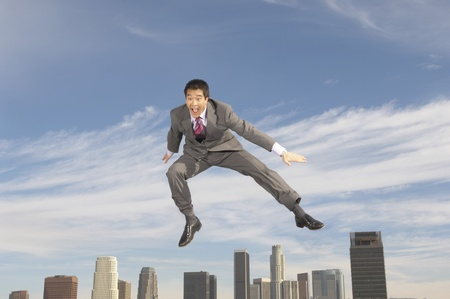 Business man jumping mid-air above city Stock Photo - 8837381