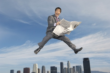 Business man reading newspaper mid-air above city Stock Photo - 8837382