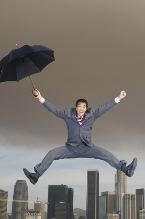Business man jumping mid-air with umbrella above city Stock Photo - 8837383