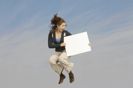 midair: Woman holding blank sign mid-air outdoors