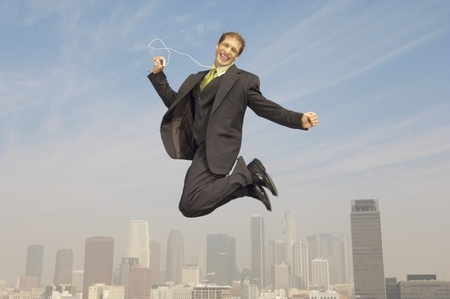 Business man listening to mp3 player mid-air above city Stock Photo - 8837385