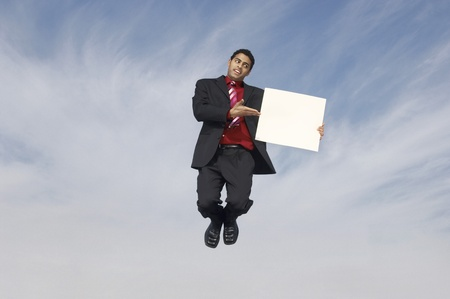 Business man jumping with blank sign outdoors Stock Photo - 8837386