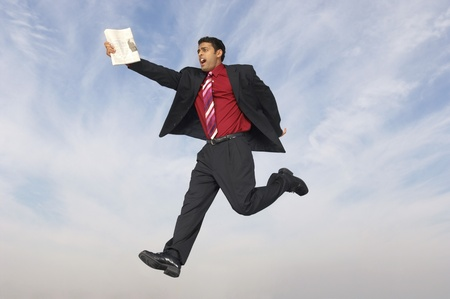 Business man running with newspaper mid-air outdoors Stock Photo - 8837387