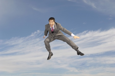 Business man crouching mid-air outdoors Stock Photo - 8837388