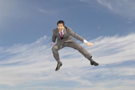 midair: Business man crouching mid-air outdoors