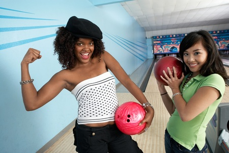 Young women at bowling alley holding balls and posing portrait Stock Photo - 8837399