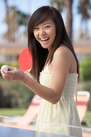 Woman in summer dress playing ping pong Stock Photo - 8837414