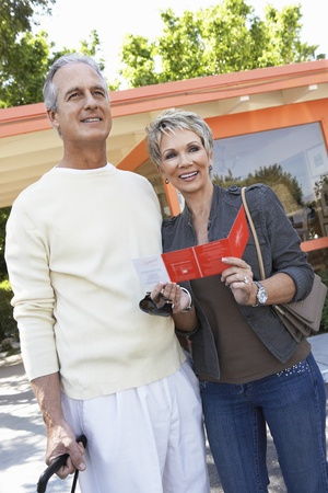 Mature couple holding suitcase and brochure outside Stock Photo - 8837480
