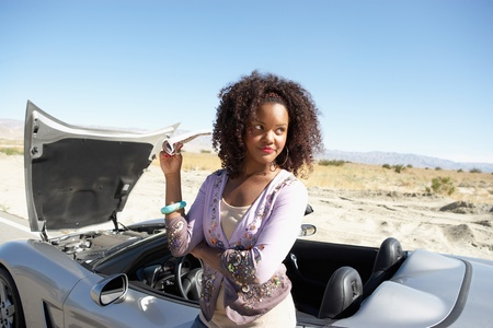 Woman standing by broken down sports car at side of desert road Stock Photo - 8837483