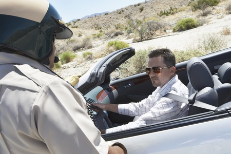 pulled over: Police officer standing by man in pulled over car on desert highway