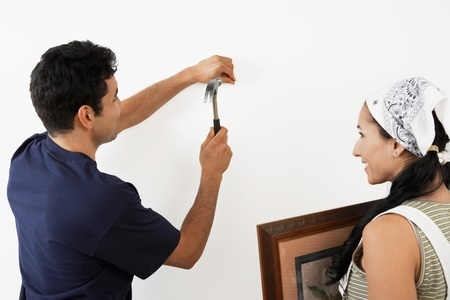 Couple hanging picture on interior wall back view Stock Photo - 8837493