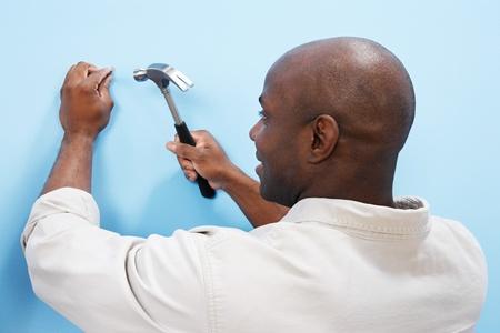 hammering: Man hammering nail into wall back view