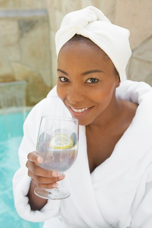 african american spa: Woman in bathrobe drinking a glass of water at spa