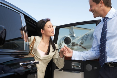 Businessman helping Woman Get Out of Car parked near private jet side view Stock Photo - 8822485