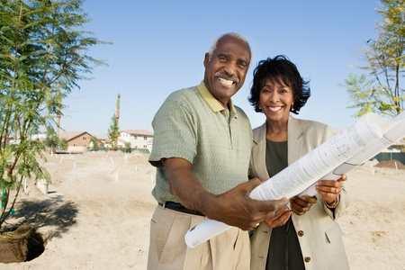 Middle-aged couple holding blueprints in vacant lot portrait Stock Photo - 8822403
