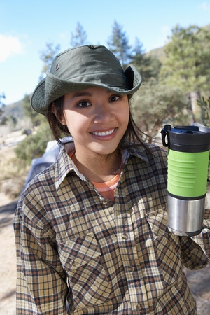 Young woman standing outdoors holding travel mug. Stock Photo