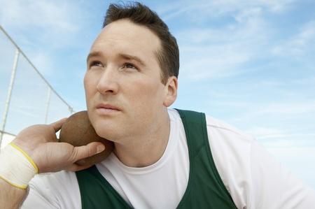 shot put: Shot Putter sosteniendo los hombros y la cabeza de lanzamiento de peso LANG_EVOIMAGES