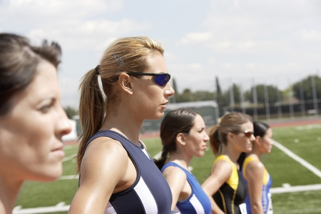 head start: Female athletes lining up to start race head and shoulders LANG_EVOIMAGES