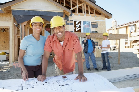 two people with others: Couple looking at blue prints of new house