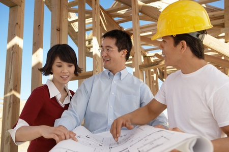 Couple looking at blue prints with builder Stock Photo - 8837515