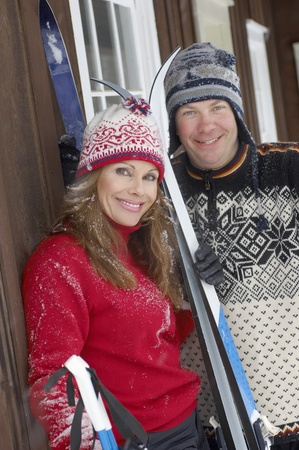 Couple standing by log cabin holding skis. Stock Photo - 8844477